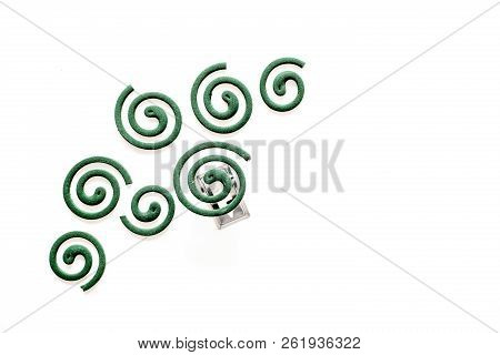 Mosquito repellent for outdoor: garden, summer house, picnic. Green spiral on white background top view copy space pattern poster