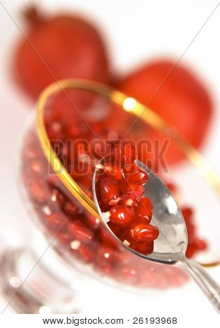 Pomegranate seeds on a spoon with a bowl and fruits behind