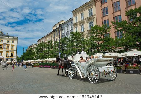 Krakow, Poland - July 8th 2018. Tourists Go On A Trip Around Old Town Krakow In A Horse Driven Carri