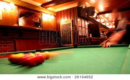 The pack scatters during a game of pool in an English pub. Deliberate motion blur.