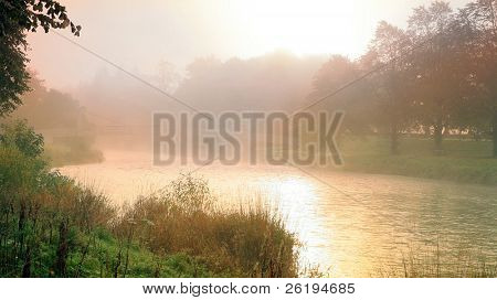 The sun breaking through  on the River Tweed in Peebles, Scotland, while the footbridge is still almost hidden in mist.