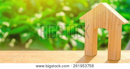 Figurine Of A Wooden House With A Large Doorway On A Green Background . Concept Of Real Estate, Purc