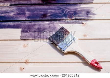 Half Painted Wooden Surface. Deep Black Color. Varnishing Natural Wood With Paint Brush.paint Wooden
