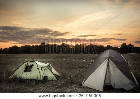 Camping Tents On Camping Sites On Summer Flatland Field Plain And Dramatic Sunset Sky During Camping