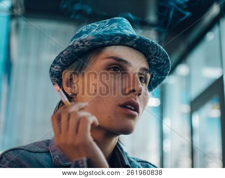 Street portrait of a smoking woman, feeling lonely,sad woman concept