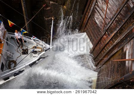 EIDSFOSS, NORWAY - JULY 18, 2018: M/S Henrik Ibsen ferry boat waiting in the lock chamber while the chamber is filled up with water at Eidsfoss lock on the Telemark Canal that connects Skien to Dalen