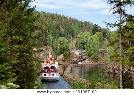 ULEFOSS, NORWAY - JULY 18, 2018: M/S Henrik Ibsen ferry boat at lower canal of the Vrangfoss lock during a unique historical boat trip through spectacular Norwegian nature by the Telemark Canal