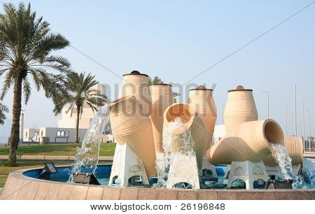 The landmark water-pots fountain on the Corniche road in the centre of Doha, Qatar, Arabia. The Islamic museum is in the background.
