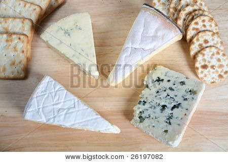 Four gourmet cheeses with biscuits on a cheeseboard. poster