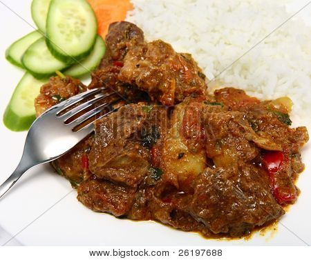 A plate of traditional mutton vindaloo, served with rice and a salad of cucumber and carrot.