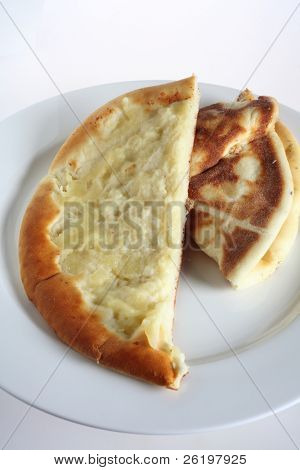 A fataya bread with halloumi cheese topping - Arabia's answer to the pizze - on a white plate. This Arabic flat bread with a topping baked into it is a popular take-away snack in the Middle East.