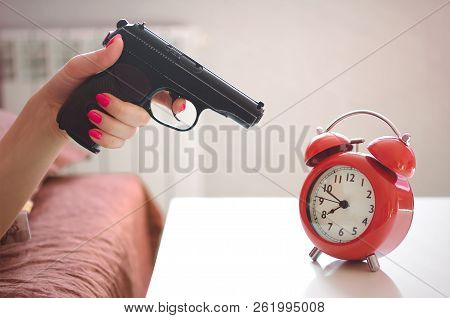 Sleepy Woman In The Bed Is Trying To Kill A Red Alarm Clock On The Table By The Gun In Her Hand. Kil