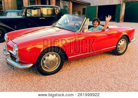 Montagnana, Italy August 27, 2018: Girl Driving Retro Car Alfa Romeo Convertible 1961 Ode Release.