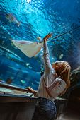 Young girl standing outstretched against aquarium glass fascinated by ocean world and touches the fishes in an oceanarium tunnel. poster