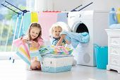 Children in laundry room with washing machine or tumble dryer. Kids help with family chores. Modern household devices and washing detergent in white sunny home. Clean washed clothes on drying rack. poster