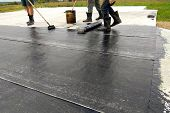 Roofer worker painting bitumen praimer at concrete surface by the roller brush Waterproofing poster