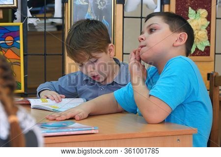 Chapaevsk, Samara Region, Russia - Circa February, 2020: Two School Children Sit At A Desk With Book