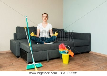 A Housewife Is Meditating After Cleaning. Woman Is Ready To Clean House. A Housewife With Detergent.