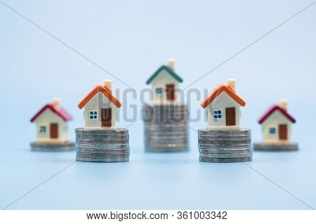 Miniature Houses Among Pile Of Coins, Housing Industry Mortgage Plan And Residential Tax Saving Stra