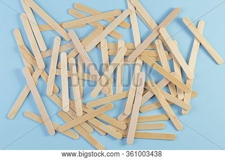 Wooden Ice Cream Stick On Blue Background. A Pile Of The Wooden Sticks. Popsicle Stick