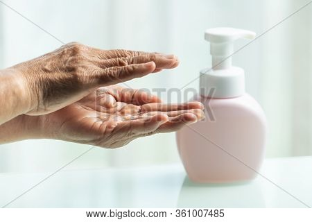 Covid-19 Coronavirus Hand Cleansing Concept, Senior Hand Apply Alcohol Gel Or Anti Bacteria Soap To