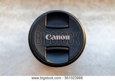 Brecht, Belgium - Februari 1 2020: A Close Up Portrait Of A Canon Lens Cap Lying On A Stone Tablet.
