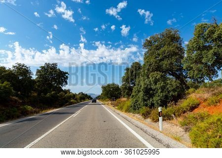 Andalusian Summer Landscape With Cork Oak Groves And Blue Sky With High White Clouds