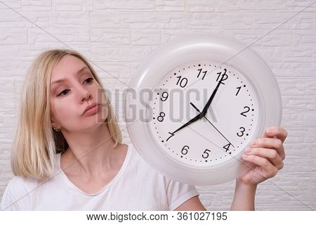 Woman Holding Clock Showing 7 Am In The Morning, Punctuality And Discipline Concept.