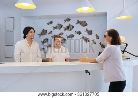 Guest Checking In To Hotel, Male And Female Receptionists Standing At The Front Desk Talking And Gre