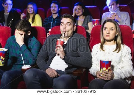 Young Scared Couple At The Cinema Watching An Horror Movie.