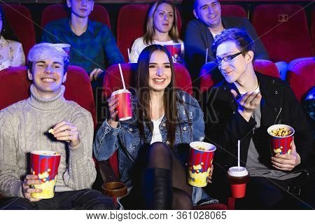 Two Young Guys And A Girl Watching A Comedy In A Movie Theater. Young Friends Watch Movies In The Ci