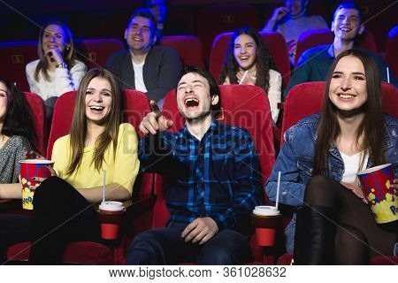 Friends Of A Guy And A Girl Are Laughing Loudly In A Movie Theater