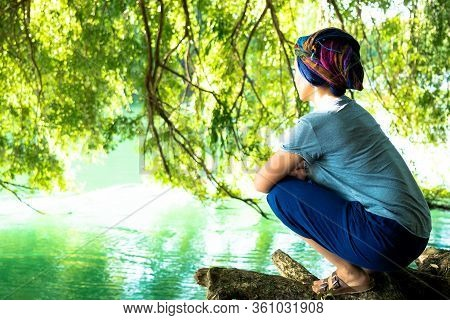 Woman With Cancer Watches The River With Her Headscarf On.