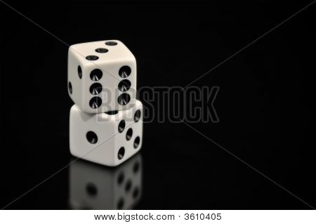 Two White Dice Stacked On Top Of Each Other And Isolated On A Black Background With A Soft Reflectio
