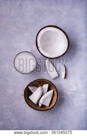 Seen From Above, On A Gray Concrete Background, Of The Coconut In Parts And In A Cold Drink In The G