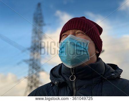 Portrait of man wearing protective respirator face mask on city street during covid-19 coronavirus pandemic virus quarantine.