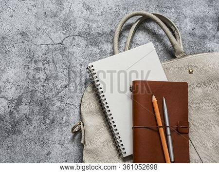 Women's Business White Leather Hand Bag With Office Accessories Notepad Organizer On A Grey Backgrou