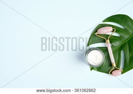 Rose Quartz Face Roller And Moisturizer Cream With Monstera Leaf On Blue Background. Flat Lay, Top V