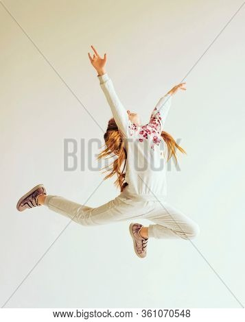Beautiful gymnast girl in grey sportswear, performing art gymnastics element, jumping, doing split leap in the air