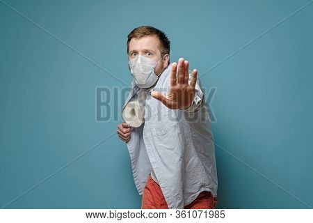 Man In A Medical Mask Hides Toilet Paper Under Shirt And Makes A Stop Gesture With Hand. Concept Of