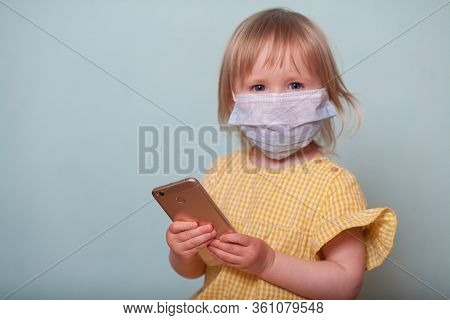 A Little Girl In A Medical Mask With A Smartphone Isolates On A Blue Background. The Concept Of Coro