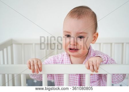 A Small Child In Pink Pajamas Is Standing In The Crib. The Kid Woke Up And Waits For His Parents To