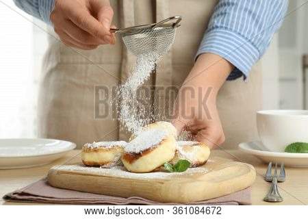 Woman Sieving Sugar Powder On Cottage Cheese Pancakes At Wooden Table, Closeup