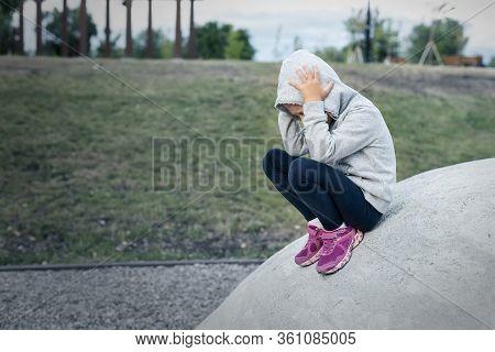 Upset Sad Depressed Little School Girl Sitting Alone At City Street Park Clutching Head. Upset Stres