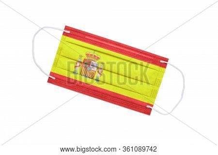 Medical Face Mask With Flag Of Spain Isolated On A White Background. Pandemic Concept In Spain. Attr