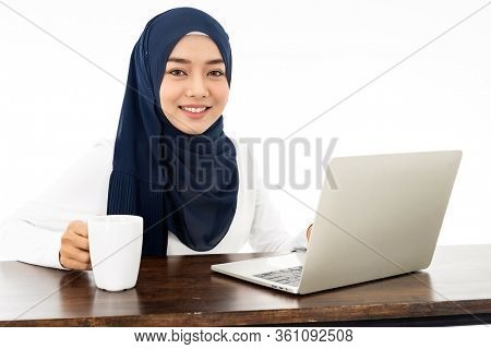 Asian young adult woman wearing hijab Working from home using laptop search and doing office work isolated in white background - office, business, finance and work station concept