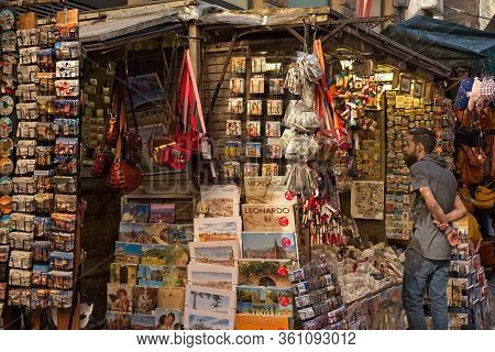 Florence, Italy - May 31, 2019: A Young Man Looks At Some Of The Merchandise On Display At A Tourist