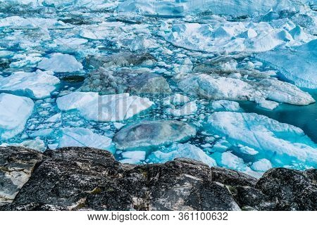 Greenland melting iceberg icefjord aerial top view of blue ice. Climate change in the Arctic. Drone picture of Ilulissat.
