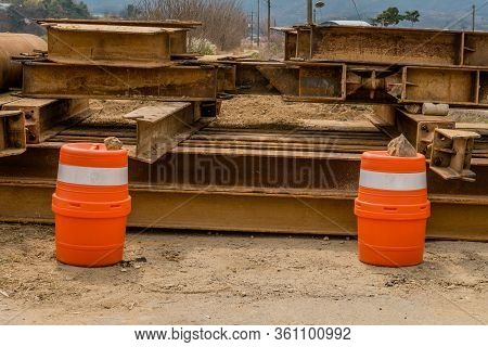 Two Orange And White Traffic Barrels In Front Of Stack Of Steel Girder Beams Beside Dirt Road.