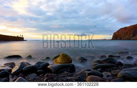 The Atlantic ocean and stones on the beach at sunset in Tenerife island, The Canaries - Long exposition